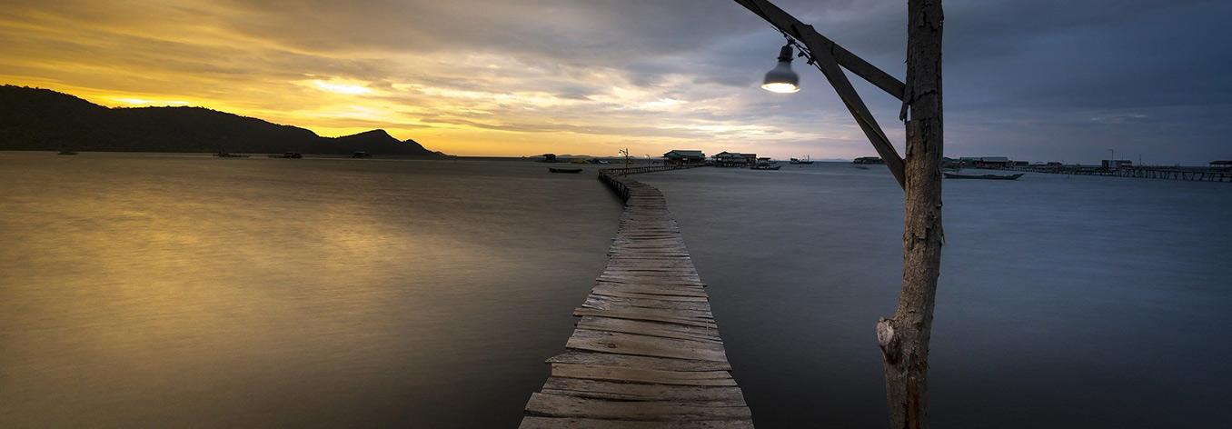 Photographie d'un pont de bois à l'aube.